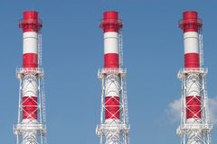 Three industrial color pipes on blue sky. Three industrial red and white pipes on blue sky Stock Images