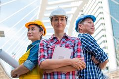 Three Industrial engineer wear safety helmet engineering standing with arms crossed on building outside. Engineering tools and co. Nstruction concept stock photos