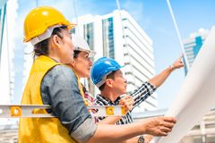 Three industrial engineer wear safety helmet engineering working and talking with drawings inspection on building outside. Engineering tools and construction royalty free stock photography