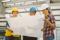 Three industrial engineer wear safety helmet engineering working and talking with drawings inspection on building outside stock photos