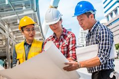 Three industrial engineer wear safety helmet engineering working and talking with drawings inspection on building outside. Engineering tools and construction stock photos