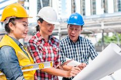 Three industrial engineer wear safety helmet engineering working and talking with drawings inspection on building outside. Engineering tools and construction stock images