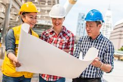 Three industrial engineer wear safety helmet engineering working and talking with drawings inspection on building outside. Engineering tools and construction royalty free stock photos
