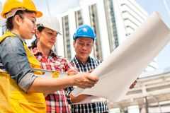 Three industrial engineer wear safety helmet engineering working and talking with drawings inspection on building outside. Engineering tools and construction royalty free stock image