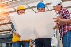 Three industrial engineer wear safety helmet engineering working and talking with drawings inspection on building outside. Engineering tools and construction royalty free stock images