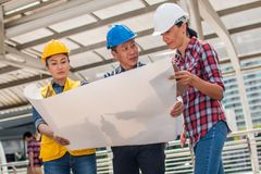 Three industrial engineer wear safety helmet engineering working. And talking with drawings inspection on building outside. Engineering tools and construction royalty free stock photography
