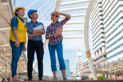 Three industrial engineer wear safety helmet and holding tablet engineering working and talking with drawings inspection. On building outside. Engineering tools stock photo