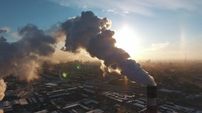 Three industrial white and red pipes smoke against contrasting sun. stock video footage