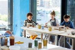 Kids in workshop. Three intercultural kids in aprons sitting by table and making handcraft from clay Stock Images