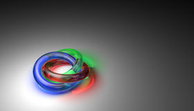 Three interlocking colored glass rings. Three interlocking transparent colored glass rings with reflective surfaces and refracted light on the background ( Royalty Free Stock Photos