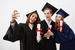 Three international graduate friends rejoicing in mantles making a selfie on a phone. Future specialists or medics Royalty Free Stock Photography