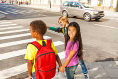 Three international kids ready to cross road Royalty Free Stock Image