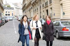 International students learning English and walking outside in. Three international students learning English and passing in  . Concept of language courses and Royalty Free Stock Photography