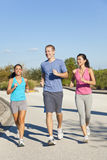 Three Interracial Adult Friends Running Jogging Stock Image
