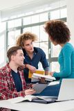 Three involved students sharing ideas and opinions about different topics. And new information learned during courses at the university Royalty Free Stock Photo