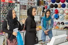 Three Iranian women are trading in the store, Isfahan, Iran. Isfahan, Iran - April 24, 2017: Iranian girl, woman and elderly woman are selling in the store hats Royalty Free Stock Photos