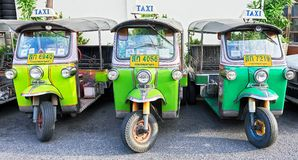 Three isolated green colored Tuk-Tuk vehicles in Bangkok stock images