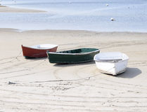 Three isolated dinghies or skiffs on Maine Coast. Red, Green and a White skiff or dinghy rest on the Maine coast while waiting to take lobster men out to their Royalty Free Stock Photos