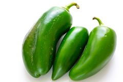 Three jalapeño peppers on a white background waiting to be used by the chef. stock images