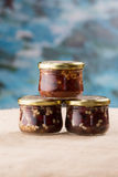 Three jam jars with berries and pine nuts. Sacking and blue background Royalty Free Stock Images