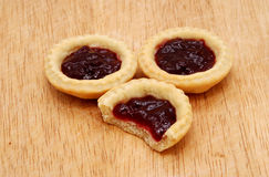 Three jam tarts, one with a bite taken, on a wooden table Royalty Free Stock Images