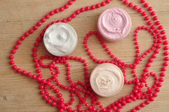 Three jars of body lotion displayed with strings of pink beads Royalty Free Stock Photos