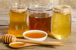 Three jars,the bowl, the spoon with a honey Royalty Free Stock Photos