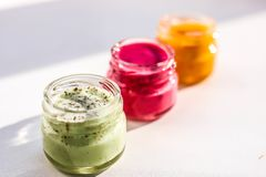 Three jars of colorful jams. Green red and yeallow honey souffle royalty free stock photos
