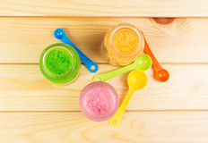Three jars  different baby puree, spoon on  background  light wood. Royalty Free Stock Image