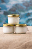 Three jars of fresh natural yogurt. Or bear, badger fat or white cream close-up sacking and blue background stock photography