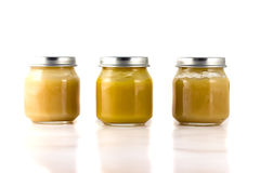 Three jars of fruit puree in a row. On a white background Royalty Free Stock Photos