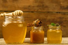 Three jars of honey with drizzler, cinnamon, flowers on wooden background Stock Image