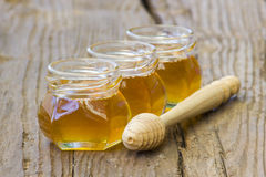 Three jars of honey and wooden dipper royalty free stock photography