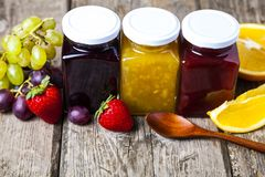Three jars with jam and spoon. On a wooden background. Delicious dessert and fresh fruits close-up Stock Photos