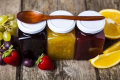 Three jars with jam. And spoon on a wooden background. Delicious dessert and fresh fruits close-up Royalty Free Stock Images