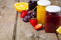 Three jars with jam. On a wooden background. Delicious dessert and fresh fruits close-up Royalty Free Stock Photos