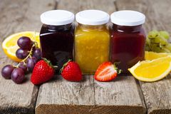 Three jars with jam. On a wooden background. Delicious dessert and fresh fruits close-up Stock Photo