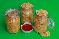 Three jars of pasta with red sauce bowl. Different sizes of pasta to choose from confined in glass jars with bowl of red sauce Stock Photo