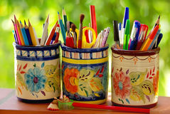 Three jars,  pencils and school objects. On a green background Royalty Free Stock Photo
