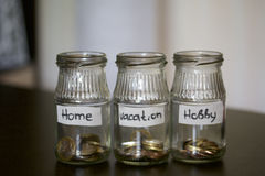Three jars - piggy bank. In the miscellaneous expenses. They are glued to the tape to write her goal of spending. At the bottom po Royalty Free Stock Images