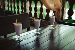 Three jars of pink berry milkshakes with straws on old wooden table. stock photography