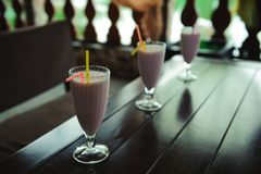 Three jars of pink berry milkshakes with straws on old wooden table. stock photos