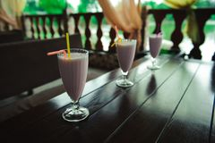 Three jars of pink berry milkshakes with straws royalty free stock images