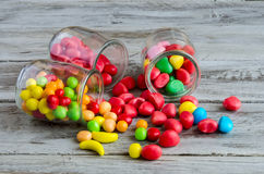 Three jars on table with scattered candies Royalty Free Stock Photos