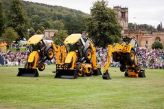 Three JCB Backhoe loaders with vehicle passing underneath them, dancing diggers stock photo