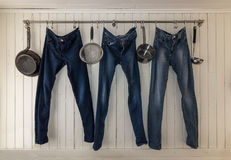 Three jeans hanging on a kitchen rail to dry Royalty Free Stock Image