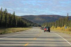 THREE JEEPS ON HIGHWAY IN CONVOY. With Evergreen lined road Stock Photo