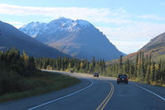 THREE JEEPS ON MOUNTAIN HIGHWAY SNOW PEAKS FORREST. Three Jeeps travelling in a convoy on Mountain Highway towards snow peaked mountains. Roadside is lined with Stock Photos