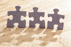 Three Jigsaw Puzzle Pieces on Table Royalty Free Stock Photo