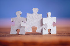 Three jigsaw puzzle pieces on a table. Joint together over blue background. Shallow depth of field Stock Images